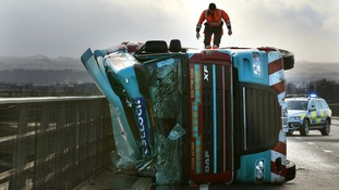 A man climbs on a lorry on its side after being blown over in strong winds on the Clackmannanshire Bridge over the Firth of Forth, Scotland, as high winds have brought another day of disruption to Britain's transport networks as warnings remain in place for fierce gusts, snow and ice over much of the weekend.