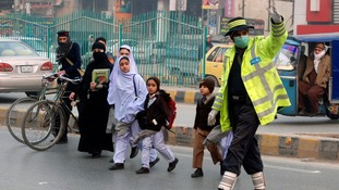 Schoolchildren walk past a traffic policeman as they cross the road while heading to school in Peshawar