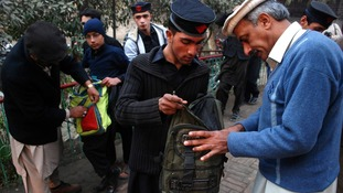 Students get their bags checked by school security staff at a school
