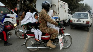 Girls ride on a motorcycle while heading to school after it reopened in Peshawar