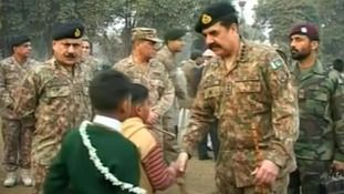 Pakistani army chief General Raheel Sharif shakes students' hands as they arrive
