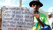 A demonstrator holds up a sign for an anti-government protest in Port-au-Prince December 5, 2014