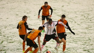 Fulham's Seko Fofana takes on the Wolverhampton Wanderers' defenders in the snow in last night's match