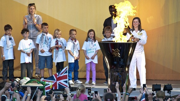 Charlotte Peck lights the cauldron with the Olympic Flame