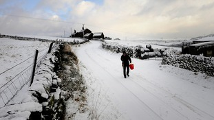 A man gritting a snow covered road near Ripponden in West Yorkshire on Saturday.