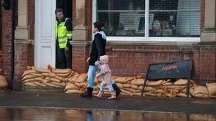 Residents walks through the flooded village of Datchet, Berkshire in February 2014