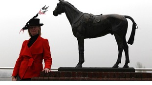 A female racegoer during day two of the 2012 Cheltenham Festival poses next to a horse