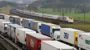A Eurostar train passes lorries parked in Operation Stack on the M20 near Ashford, Kent, as delays continue at the Channel Tunnel in Folkestone due to power supply problems.