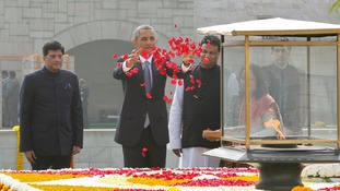 US President Barack Obama scatters rose petals at the Mahatma Gandhi memorial in New Delhi