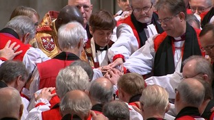 Members of the clergy gather round Rev Lane as she is ordained.