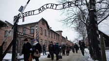 Survivors pass the main gate of the Auschwitz death camp.
