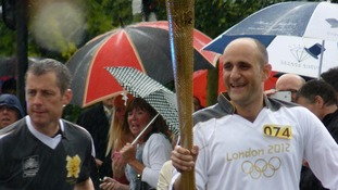 Alan Bowen takes the torch along the London Road in Leigh on Sea in the pouring rain