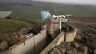 A member of the United Nations Disengagement Observer Force (UNDOF) looks through binoculars at Mount Bental, an observation post in the Israeli occupied Golan Heights January 28, 2015.