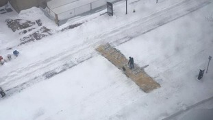 A solitary sweeper clears snow from the Boston marathon finish line.