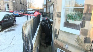 Car crashes through railings to reach basement level