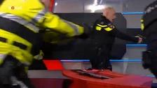 Police storm the studio.