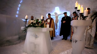 A priest leads the ceremony behind a carved ice altar
