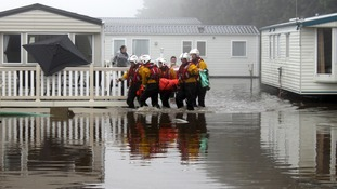 Volunteers from Filey RNLI lifeboat station and the coastguard helping to rescue people from their caravans.