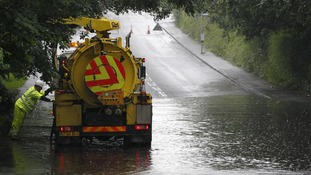 Council workers try to clear Manchester Road in Handforth, Cheshire after heavy rain caused flooding.