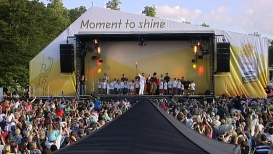 The Olympic torch is held aloft on stage.