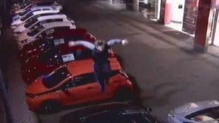 The young man can be seen jumping on the cars.