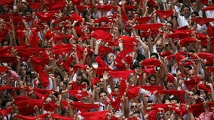 Revellers hold up their red scarves at the start of the festival.