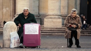 Two homeless women sit on a bench in Rome