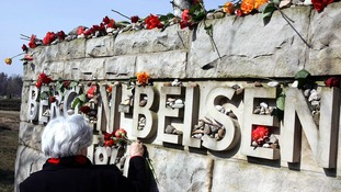 A survivor puts down flowers at a memorial stone at the Bergen-Belsen camp.