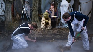Adjustments are made to a waxwork model of Yoda