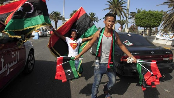Libyan national flag sellers celebrate on the street after casting their vote