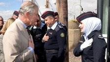 Prince Charles is greeted by a Jordanian Police woman.