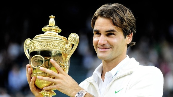 Champion Roger Federer holds the trophy after his victory on Centre Court