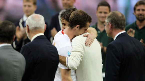 The finalists embrace after Federer beats Murray to win his seventh Wimbledon title