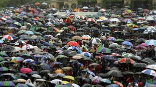 Tennis fans used umbrellas as the rain started to fall on Murray Mount in Wimbledon