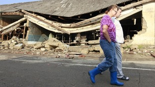 Local residents walk along a street damaged by floods in the town of Krymsk