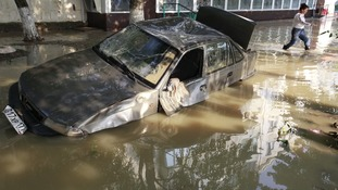 A local resident passes by a damaged car stuck in a flooded street in the town of Krymsk