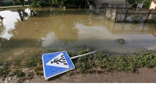 A traffic sign lays on the ground in a flooded street in the town of Krymsk in Krasnodar region