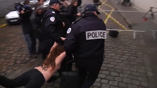 A topless protester is carried away by police in Lille.