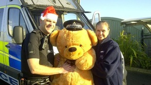 PC Nick Gravenor from Weymouth police hands over the giant teddy bear to Penny Corp-Palmer from Goulds Garden Centre, ready to be raffled off.