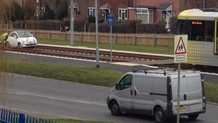 A car on the tracks with a tram stopped nearby.