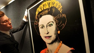 An employee of Bonhams Auctioneers adjusts a print by Andy Warhol of The Queen.