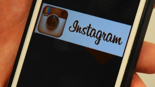The Instagram logo is shown on an Apple iPhone 5S