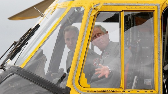 Duke of Cambridge shows the Prince of Wales one of the Sea King helicopters he captains during a tour of RAF Valley on Anglesey