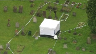 A forensic officer works in a cordon in the churchyard at All Saints Church in Writtle, Chelmsford.