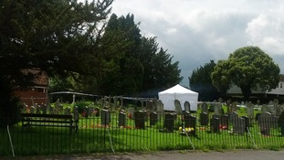 A white tent in a church yard in Writtle, Essex where the body of a man suspected of shooting an off-duty police officer was found.