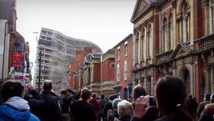The shot shows crowds of people looking on from Pocklingtons Walk as the towers tumbled