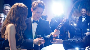Eddie Redmayne looks at his Best Actor Oscar after it was engraved with his name