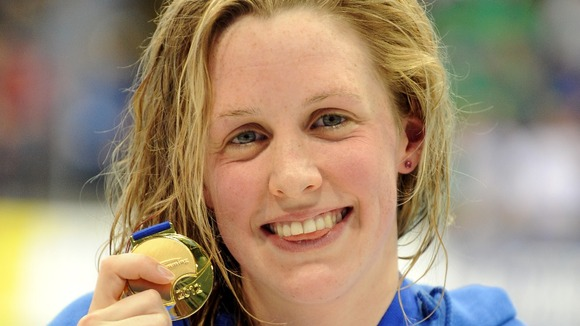 Hannah Miley celebrates with her gold medal after victory in the women&#x27;s 200m individual medley at the British Gas Swimming Championships.