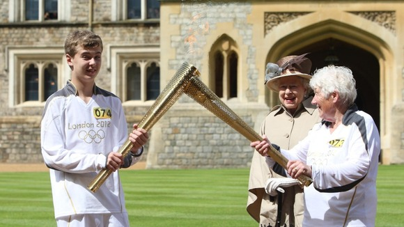 Gina Macgregor (right) passes the Olympic flame to torchbearer Phillip Wells.