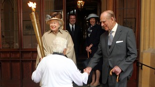 The Queen looks at the Olympic flame as the Duke of Edinburgh shakes hands with torchbearer Gina Macgregor at Windsor Castle.